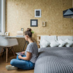Student woman sitting on the floor in her bedroom